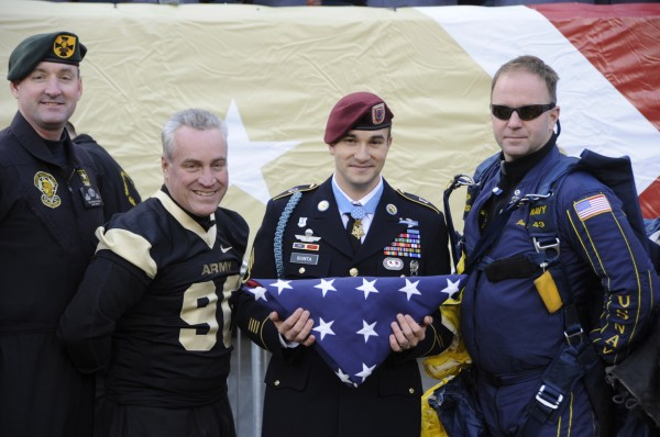 SSG Salvatore Giunta, a medal of honor winner, is presented with a flag at the Army vs. Navy game